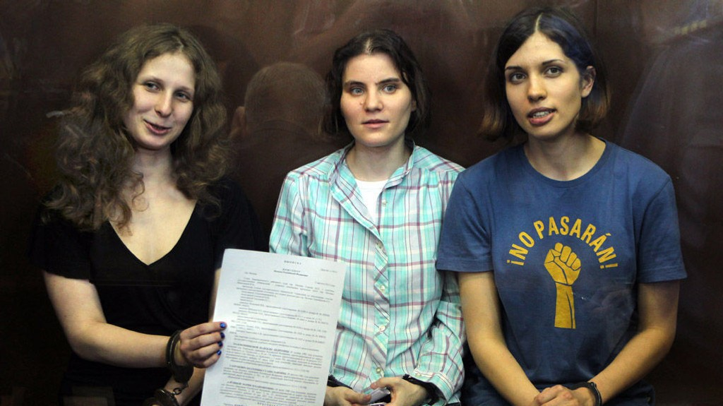 Maria Alekhina, Yekaterina Samutsevich, og Nadezhda Tolokonnikova viser frem rettens kjennelse fra glassburet.