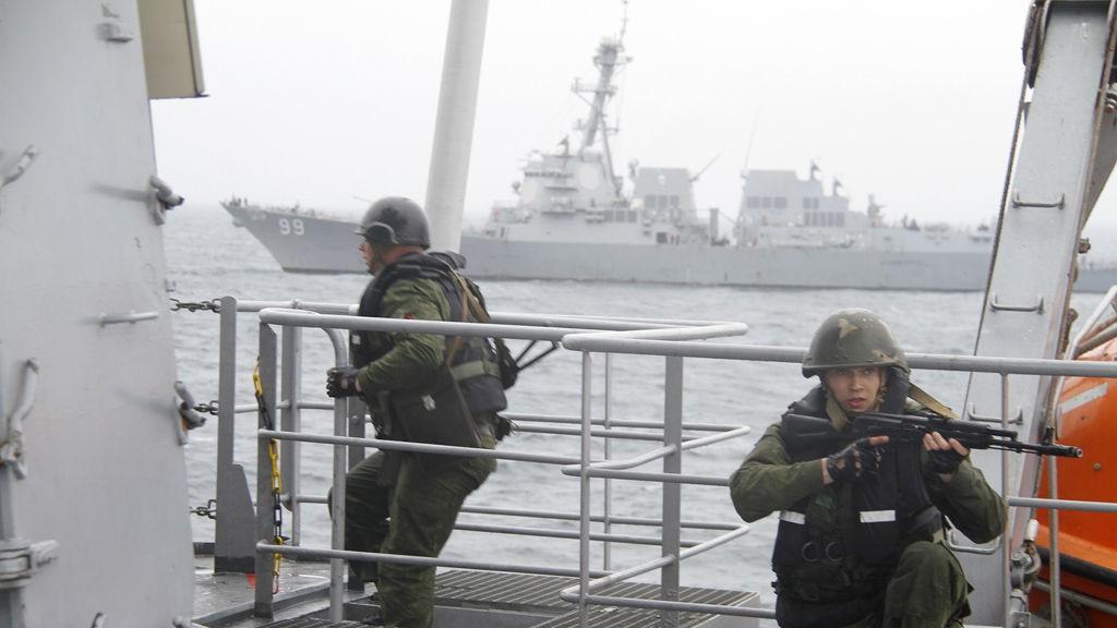 Russiske bordingsstyrker tar seg frem mot broen på KV Nordkapp under marineøvelsen Northern Eagle vest for Værøy tirsdag, mens den amerikanske destroyeren USS Farragut sees i bakgrunnen.